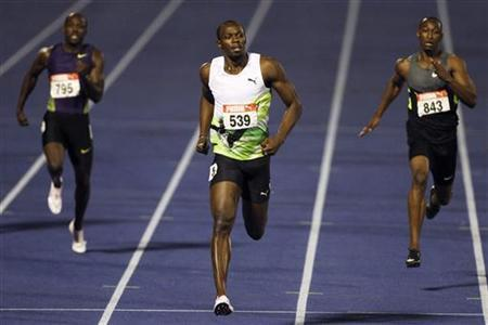 Usain Bolt (C) runs during the men's 200 meters semi-final at the Jamaican Olympic trials in Kingston city, June 30, 2012. REUTERS/Ivan Alvarado
