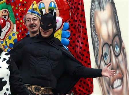 A reveler dressed as Batman gestures beside a caricature of Germany's Defence Minister Karl-Theodor zu Guttenberg (R) as they attend a carnival parade in Berlin, in this February 27, 2011 file photo. REUTERS/Thomas Peter/Files