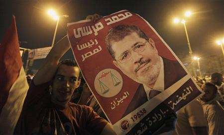 A supporter of Egypt's first Islamist President Mohamed Mursi cheers with a poster of Mursi at Tahrir Square in Cairo July 9, 2012. REUTERS/Mohamed Abd El Ghany