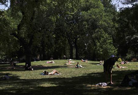 People sunbathe at Tompkins Square Park in New York July 8, 2012. REUTERS/Shannon Stapleton