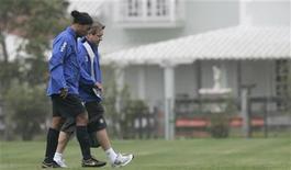 Ronaldinho Gaúcho deixa um dos campos da Granja Comary acompanhado do fisioterapeuta Luis Rosan, durante treino da seleção brasileira em novembro de 2007. 15/11/2007 REUTERS/Bruno Domingos
