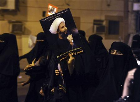 A protester holds up a picture of Sheikh Nimr al-Nimr during a rally at the coastal town of Qatif, against Sheikh Nimr's arrest July 8, 2012. REUTERS/Stringer