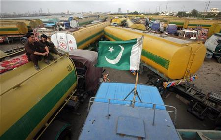 A Pakistan national flag is mounted on the top of a fuel tanker, which was used to carry fuel for NATO forces in Afghanistan, as drivers sit nearby, at a compound in Karachi July 3, 2012. REUTERS/Athar Hussain