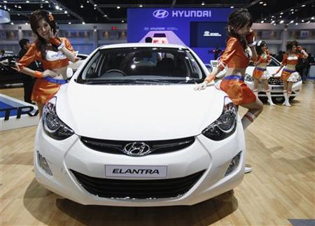 Models pose beside a Hyundai Elantra during a media presentation of the 33rd Bangkok International Motor Show in Bangkok March 27, 2012. REUTERS/Chaiwat Subprasom