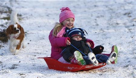 Youngsters toboggan in the snow, in Princes Risborough, southern England January 5, 2009. REUTERS/Eddie Keogh