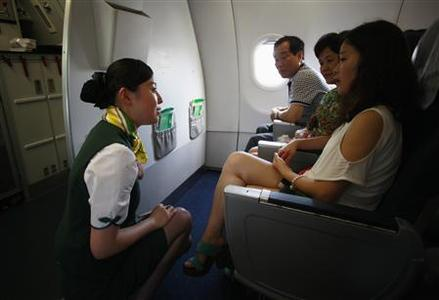 A crew member of Spring Airlines talks with travelers onboard an Airbus A320 aircraft at Hongqiao airport in Shanghai July 6, 2012. REUTERS/Aly Song
