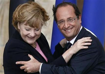 France's President Francois Hollande (R) and German Chancellor Angela Merkel smile after kissing each other during the 50th anniversary ceremony of the reconciliation meeting between former French president Charles de Gaulle and German Chancellor Konrad Adenauer after World War Two, in Reims July 8, 2012. REUTERS/Jacky Naegelen