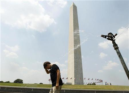 Timmy Doyle refreshes himself at a sprinkler as he passes by the Washington monument in Washington June 21, 2012. REUTERS/Jose Luis Magana