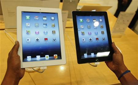 A man inspects the Apple New iPad (L) next to an iPad 2 at an electronics store in Mumbai April 27, 2012. REUTERS/Vivek Prakash