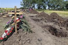 Ряды свежих могил на кладбище в Крымске в понедельник, 9 июля 2012 года. Принявший основной удар наводнения на юге России Крымск на четвертый день после трагедии наполнился гуманитарной помощью и волонтерами. Жители города, скованного липкой жарой и тяжелым запахом гнили, во вторник разгребали завалы, стояли в очередях за прививками и одного за другим отпевали и хоронили погибших. REUTERS/Eduard Korniyenko