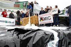"""Productores de leche vertieron el martes miles de litros de leche fuera del Parlamento Europeo en Bruselas, creando """"lago de leche"""" para protestar contra los bajos precios. En la imagen, un productor de leche vierte leche en un estanque improvisado frente al Parlamento Europeo en Bruselas, el 10 de julio de 2012. REUTERS/Francois Lenoir"""