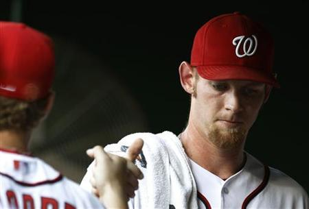 Washington Nationals starting pitcher Stephen Strasburg (R) is greeted in the team dugout prior to his MLB baseball game against the Colorado Rockies in Washington July 6, 2012. REUTERS/Gary Cameron