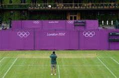 Um trabalhador fotografa a quadra enquanto lonas com o símbolo das Olimpíadas são erguidas no All England Lawn Tennis Club (AELTC), preparando-se para receber os Jogos Olimpímpicos de Londres. O Comitê Organizador dos Jogos de Londres-2012 (Locog) assumiu o controle das quadras de tênis mais famosas do mundo nesta terça-feira, 18 dias antes de tenistas como os campeões de Wimbledon este mês Roger Federer e Serena Williams, e o vice-campeão Murray, começarem a disputa pelas medalhas. 10/07/2012 REUTERS/Ki Price