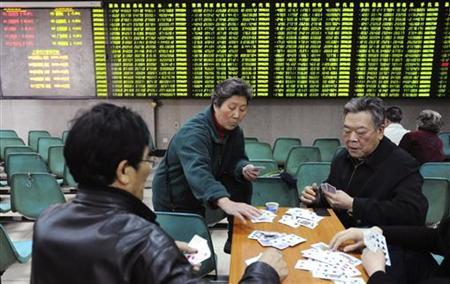 Investors play cards in front of an electronic board showing stock information filled with green-coloured figures, which indicate falling prices, at a brokerage house in Nanjing, Jiangsu province March 28, 2012. REUTERS/Leo Lang