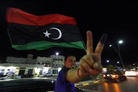 A man, with an inked finger, flashes the victory sign as he celebrates with the new Libyan flag at the end of voting day in Sirte July 7, 2012. REUTERS/Anis Mili