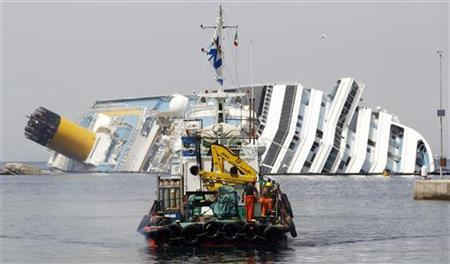 A boat with rescue workers sails in front of capsized cruise liner Costa Concordia near the harbour of Giglio Porto June 20, 2012. REUTERS/Max Rossi