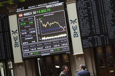 Traders talk as the IBEX 35 session is displayed on an electronic board at Madrid's stock exchange June 29, 2012. REUTERS/Susana Vera