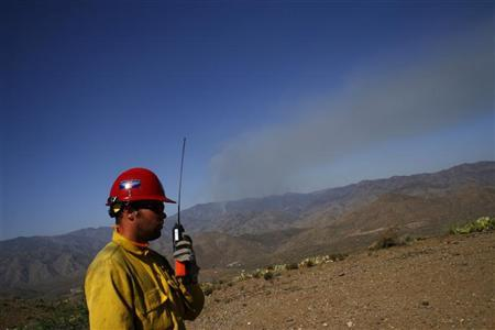 A firefighter talks on his remote radio as smoke from the Gladiator Fire is visible in Cleator, Arizona May 17, 2012. REUTERS/Joshua Lott