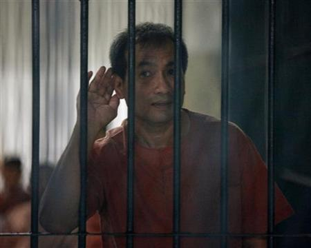 Lerpong Wichaikhammat, who goes by the name of Joe Gordon, gestures as he waits in a prison cell at the Bangkok Criminal Court December 8, 2011. REUTERS/Chaiwat Subprasom/Files