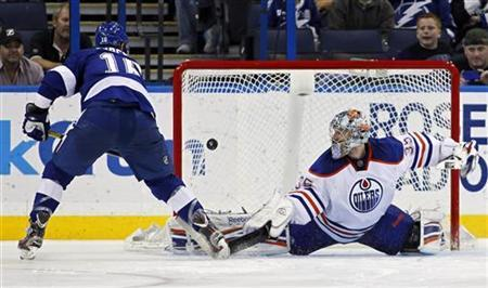 Tampa Bay Lightning's Teddy Purcell (L) shoots past Edmonton Oilers goalie Nikolai Khabibulin during the shootout in their NHL hockey game in Tampa, Florida March 22, 2012. REUTERS/Mike Carlson
