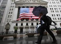 """Мужчина проходит под зонтом мимо фондовой биржи в Нью-Йорке, 4 июня 2012 года. Агентство Fitch Ratings во вторник подтвердило кредитный рейтинг США на уровне """"ААА"""" и сохранило негативный прогноз, указав на неспособность американского правительства согласовать меры сокращения дефицита, которая подрывает диверсифицированную и богатую экономику. REUTERS/Brendan McDermid"""