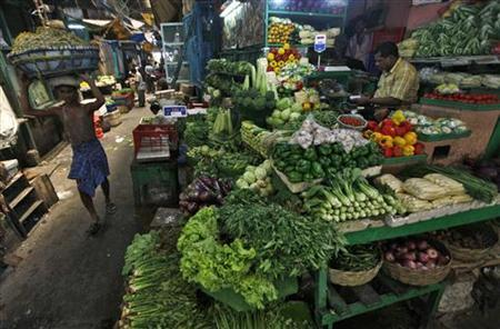 A labourer carries a packed basket of vegetables as a vendor waits for customers at his vegetables stall at a market in Kolkata May 14, 2012. REUTERS/Rupak De Chowdhuri/Files