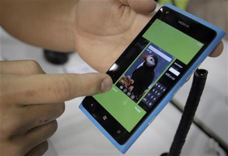 A visitor plays with a Nokia smartphone at the Windows Phone section at the Microsoft booth during the 2012 Computex exhibition at the TWTC Nangang exhibition hall in Taipei June 6, 2012. REUTERS/Yi-ting Chung/Files