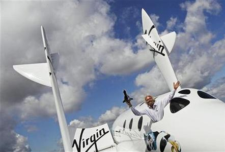 Entrepreneur Richard Branson waves a model of the LauncherOne cargo spacecraft from a window of an actual size model of SpaceShipTwo on display, after Virgin Galactic's LauncherOne announcement and news conference, at the Farnborough Airshow 2012 in southern England July 11, 2012. REUTERS/Luke MacGregor