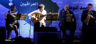 Iraqi oud player Naseer Shamma (2nd L) performs during a concert in Baghdad June 28, 2012. Many of Iraq's most talented musicians fled during the rule of Saddam Hussein, fearing persecution for their political views and suffering from a lack of funding and exposure if they refused to glorify the leader in their art. Others left after the U.S.-led invasion in 2003, escaping violence as war broke out. Concert venues were shuttered. Some musicians were threatened by the Iraqi arm of al Qaeda. Now, gingerly, some musicians are making plans to come back, hoping to revive Iraq's rich musical tradition on home soil. Picture Taken June 28, 2012. REUTERS/Thaier al-Sudani