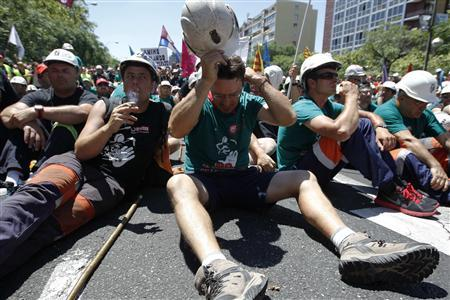 Miners sit on a street to protest against government austerity measures in Madrid July 11, 2012. Joined by supporters and trade unionists in the capital, the miners rallied noisily at the climax of a 44-day protest against a 60 percent cut in coal subsidies which they say will force mines to close and put many out of work. REUTERS/Andrea Comas