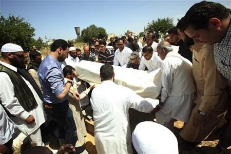 Men prepare to bury the body of former oil chief Shokri Ghanem, who defected during the anti-Gaddafi revolt last year, during a funeral ceremony at a cemetery in Tripoli May 4, 2012. REUTERS/Ismail Zitouny