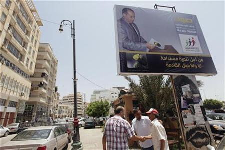 Men shake hands near an election campaign poster of a candidate running for election to Libya's National Congress, Mahmoud Jibril, head of the National Forces Alliance, in Benghazi July 9, 2012. REUTERS/Esam Al-Fetori