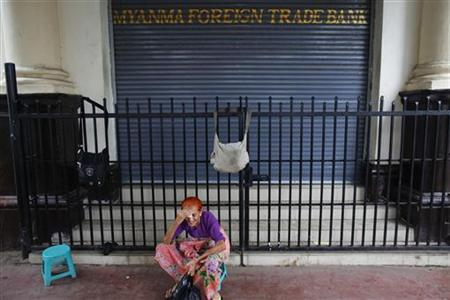 An elderly woman rests in front of a bank in Yangon May 27, 2012. REUTERS/Damir Sagolj