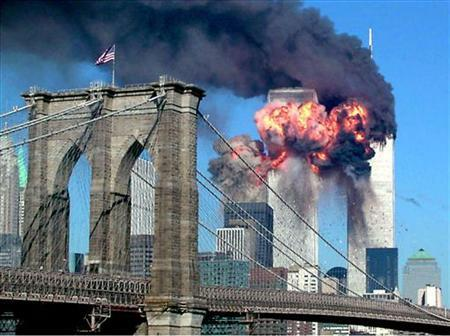 A plane explodes after hitting the second tower of the World Trade Center as the other tower burns in New York September 11, 2001 with the Brooklyn bridge in the foreground. REUTERS/Stringer/Files