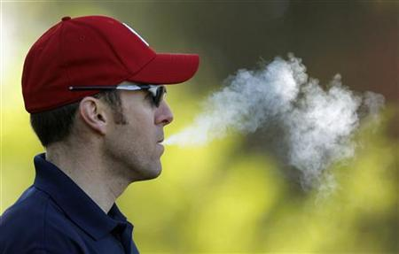 A spectator smokes during second round play in the 2010 Masters golf tournament at the Augusta National Golf Club in Augusta, Georgia, April 9, 2010. REUTERS/Brian Snyder