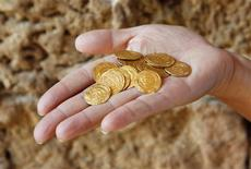 An Israel Nature and Parks Authority employee displays gold coins found hidden in a ceramic jug at the Arsuf cliff-top coastal ruins, 15 km (9 miles) from Tel Aviv, in this file pictur taken July 9, 2012. The 1,000-year-old treasure was unearthed at the famous Crusader battleground where Christian and Muslim forces once fought for control of the Holy Land. REUTERS/Baz Ratner/Files