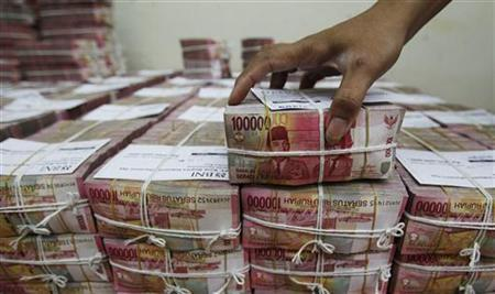 A bank employee removes a bundle of rupiah banknotes at the Bank National Indonesia (BNI) in Jakarta April 26, 2012. REUTERS/Supri