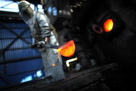A worker removes hot copper at a copper anodes and minerals plant in Paipote, Copiapo September 7, 2010. REUTERS/Carlos Barria