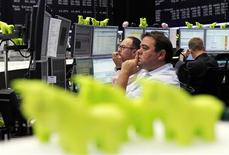 Traders work at their desks at the Frankfurt stock exchange July 11, 2012. REUTERS/Alex Domanski