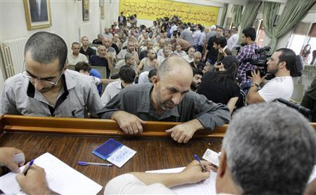 Syrians detainee, who were arrested over participation in the protests against Syrian President Bashar al-Assad's regime, are seen signing their release papers at the Damascus police leadership building July 11, 2012. REUTERS/Khaled al- Hariri