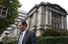 Мужчина проходит мимо здания Банка Японии в Токио, 14 октября 2009 года. Банк Японии в четверг сохранил прежнюю денежно-кредитную политику и не изменил мнение о том, что экономика страны постепенно восстанавливается. REUTERS/Issei Kato (JAPAN BUSINESS)