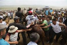 Residents touch the horse of a competitor at a horse race during the Naadam Festival in Khui Doloon Khudag, outside Ulan Bator July 12, 2012. REUTERS/B.Rentsendorj