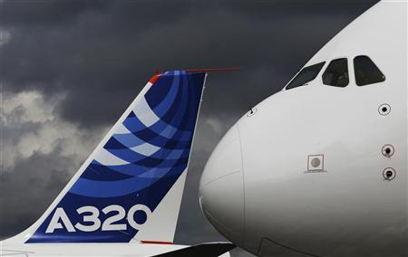 The nose cone of an Airbus A380 overlooks the tail fin of an Airbus A320 at the Farnborough Airshow 2012 in southern England July 10, 2012. REUTERS/Luke MacGregor