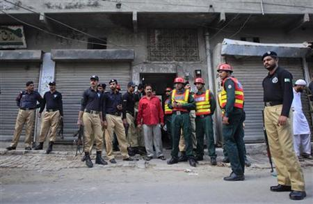 Policemen and rescue workers gather outside a building where unidentified gunmen killed police cadets in Lahore on July 12, 2012. REUTERS/Mohsin Raza