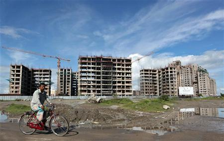 A man rides a bicycle in front of the construction site of a residential complex in Kolkata August 31, 2010. REUTERS/Rupak de Chowdhuri/Files