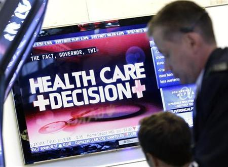Traders work on the floor of the New York Stock Exchange as a screen displays the health care decision, June 28, 2012. REUTERS/Brendan McDermid