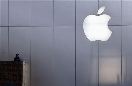 A policeman looks out from a balcony as the crowd is dispersed from the front of an Apple store in the Beijing district of Sanlitun in this January 13, 2012 file photo. REUTERS/David Gray/Files