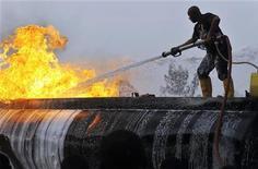 Пожарный пытается потушить огонь на загоревшейся автоцистерне на АЗС в Абудже, 24 марта 2012 г. По меньшей мере 92 человека, включая женщин и детей, погибли в четверг в результате аварии и последующего возгорания бензовоза в дельте реки Нигер, сообщил очевидец Рейтер. REUTERS/Afolabi Sotunde