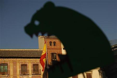 A Spanish flag is seen through a depiction of Caja Madrid bank (Bankia) during a protest against Spain's bailout at La Constitucion square in Malaga, southern Spain, June 15, 2012. REUTERS/Jon Nazca/Files