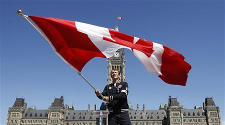 Triathlete Simon Whitfield waves the Canadian flag after being named Canada's flag bearer for the opening ceremony at the London 2012 Olympic Games, on Parliament Hill in Ottawa July 12, 2012. REUTERS/Chris Wattie